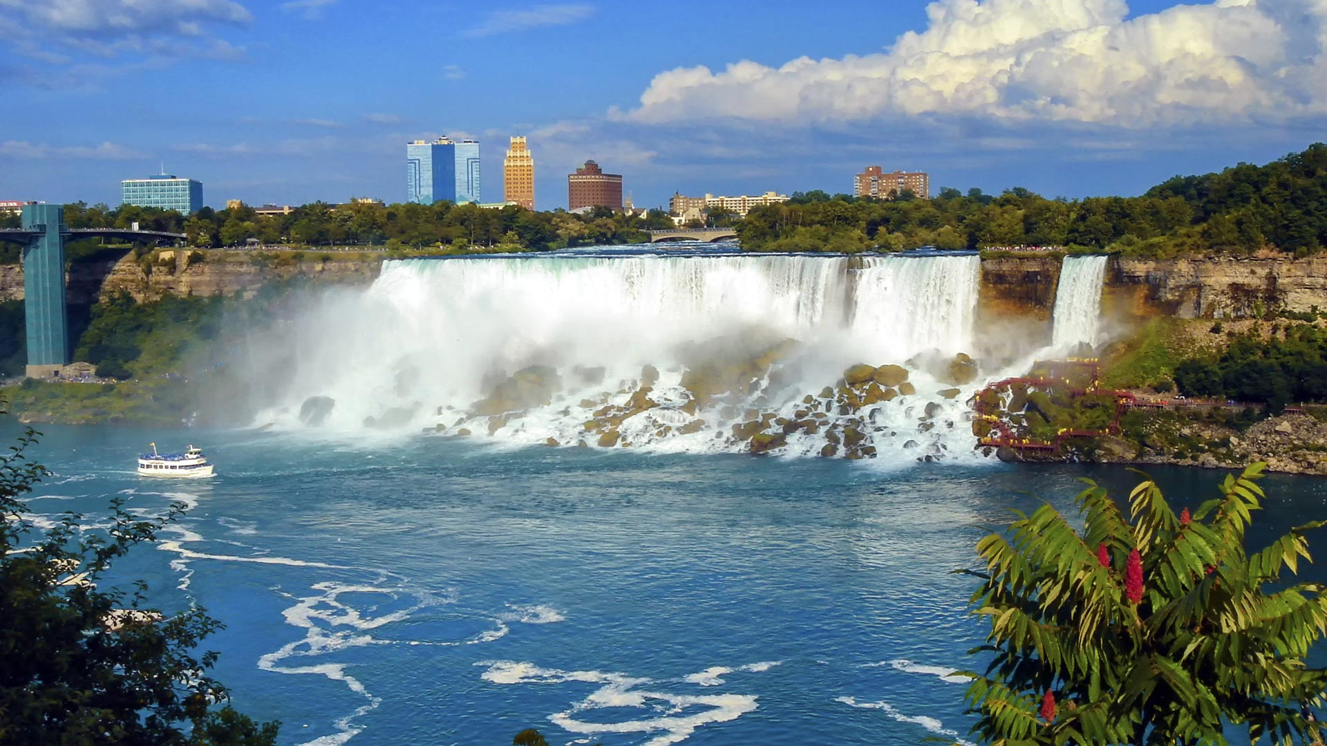 Niagara falls from Canada with boat, buildings and vegetation, Canada and USA