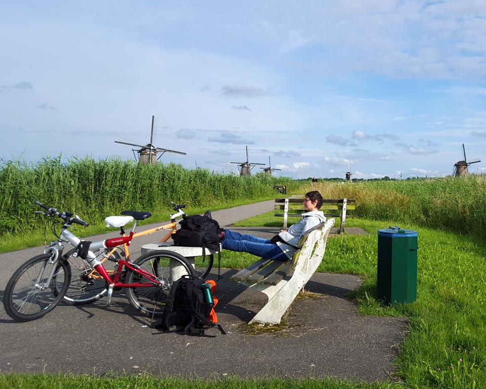 Elena having rest next to the windmills in Kinderdijk, Netherlands